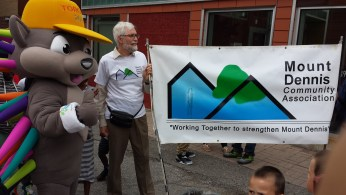 Mount Dennis Community Association banner along with Pachi for a special Pan Am event