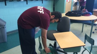 Anthony cleaning the chairs of desks in a classroom