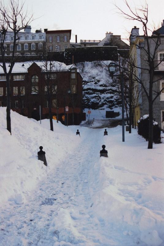 Une ruelle dans la neige au fond des murs