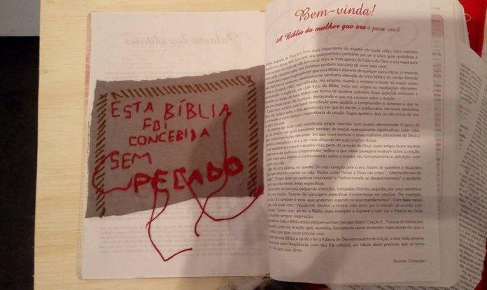 Bíblia rasgada com inscrição sarcástica colocada sobre ela, em exposição na UFPE