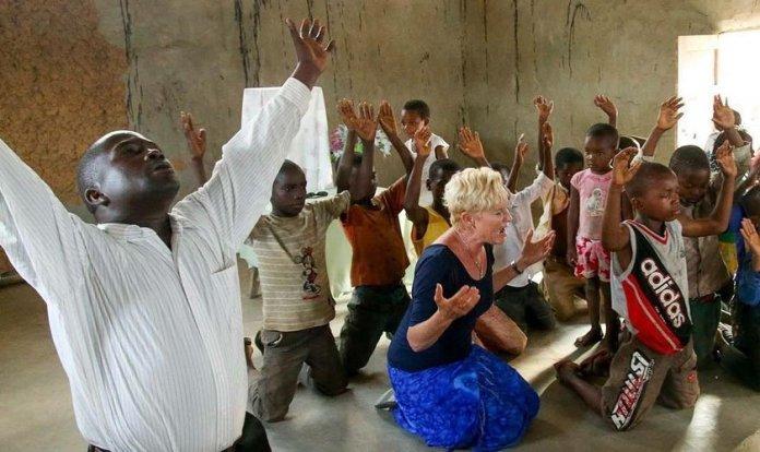Heidi Baker orando em uma província, rodeada por cristãos de Moçambique