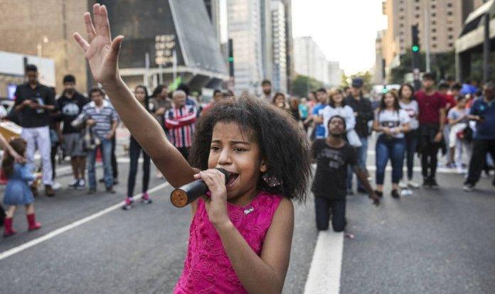 Aos 10 anos, Vitória de Deus canta e prega na Avenida Paulista. (Foto: Eduardo Knapp/Folhapress)