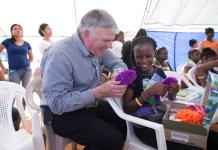 Franklin Graham entrega uma caixa de sapatos cheia de presentes da Operação Natal Infantil, em 2015