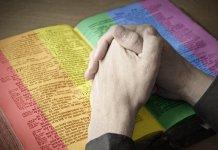 Mãos sobre uma Bíblia colorida (imagem ilustrativa)
