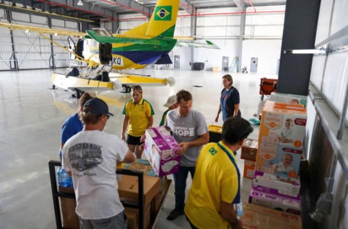 Membros da equipe de serviços internacionais de desastres da Convoy of Hope, juntamente com voluntários, desembalam suprimentos de ajuda humanitária de um avião fretado depois de chegar a Nassau, Bahamas, 7 de setembro de 2019