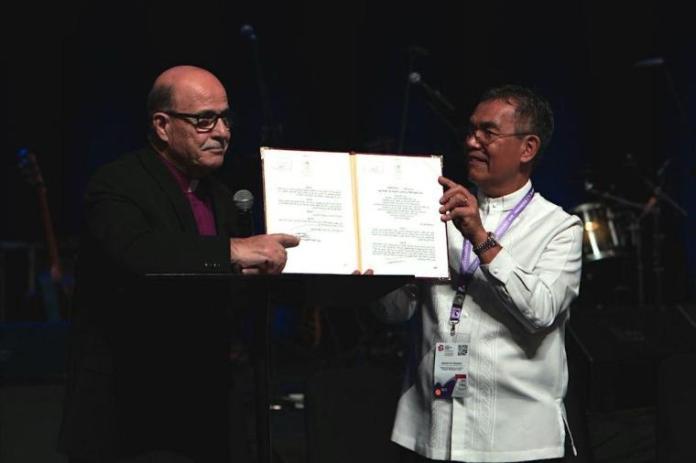Munir Salim Kakish, presidente do Conselho de Igrejas Evangélicas Locais na Terra Santa (à esquerda), e o bispo Efraim Tendero, secretário geral da Aliança Evangélica Mundial (à direita), sustentam documento da Autoridade Palestina que reconhece o grupo de Kakish (Foto: WEA)