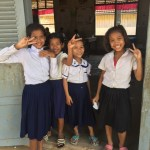 Photograph of four girls smiling, Cambodia