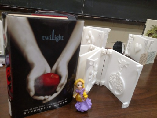 3D book and the book Twilight with a small blond doll in a purple dress