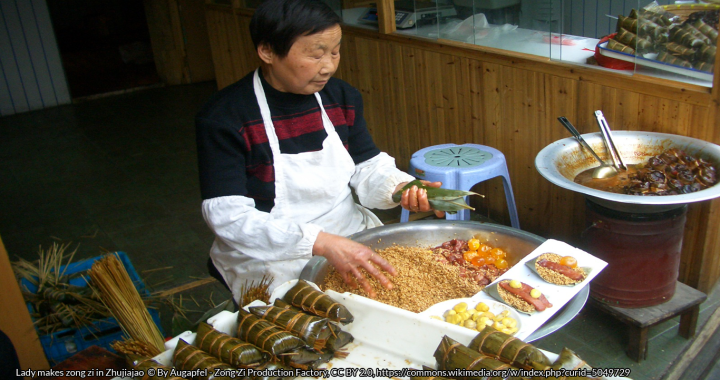 Lady makes zong zi in Zhujiajao © By Augapfel - Zong Zi Production Factory, CC BY 2.0, https://commons.wikimedia.org/w/index.php?curid=5049729