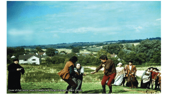 Two men pulling a woman along by the arms in a field, while a crowd looks on.