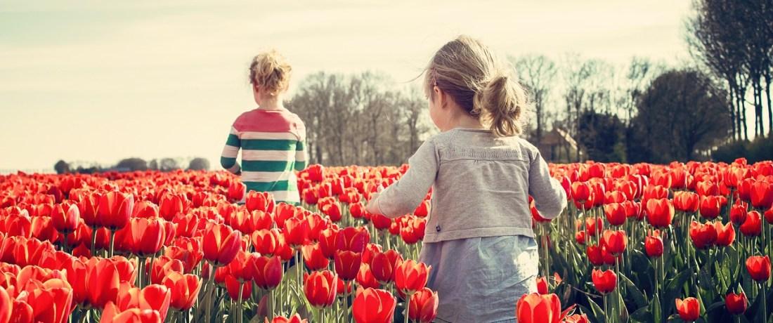 Children running through a field of flowers