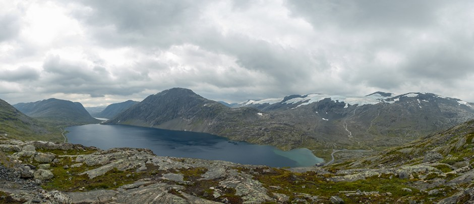 A beautiful view from the above on lake, Norway. Lake is located in between tall mountains. Slopes of the mountains are partially covered with snow. The water of the lake is navy blue