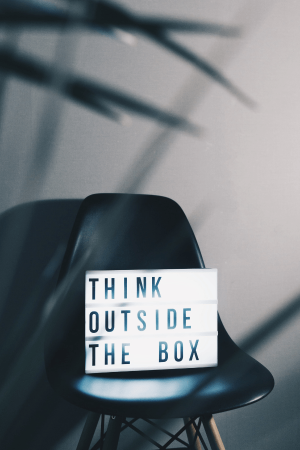 Signe Think Out The Box sur une chaise noire.