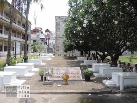 Die Ruhestätte der letzten 14 Opfer von S-21. Im Hintergrund der Galgen, der für Hinrichtungen aufgestellt wurde.