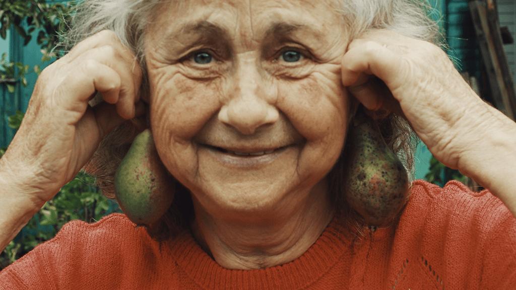 Mujer mayor divertida con peras en las orejas