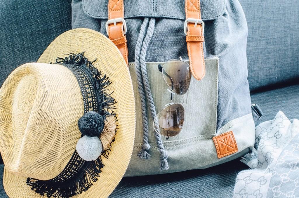 long-haul flight essentials - bag and a hat