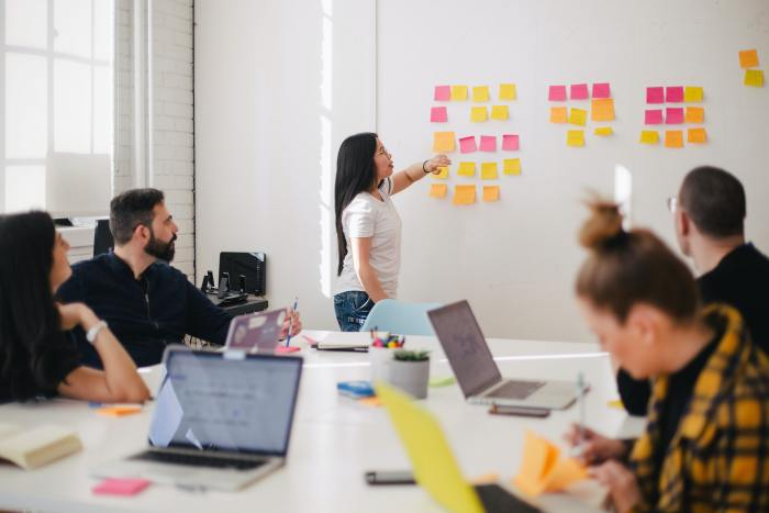 in the background a woman with brown hair is leading a meeting to plan for marketing strategy and pointing to colorful sticky notes on a white wall. In the foreground, co workers with laptops open sit around a table and watch her or take notes.