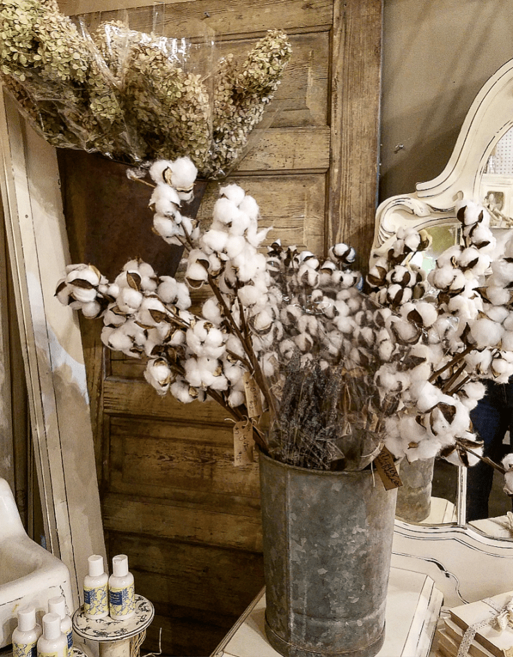 Farmhouse style booth display cotton stems salvaged door dried hydrangeas galvanized bucket