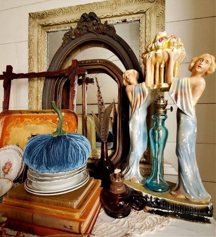 Fall vignette with unique vintage treasures art deco lamp vintage antique picture frames, vintage dishes, vintage orange books, vintage oil lamps