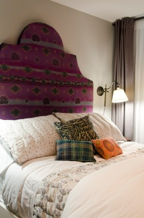 The decorative pillows and the headboard are made from repurposed Indian Saris that are quilted using a traditional type of embroidery called, kantha
