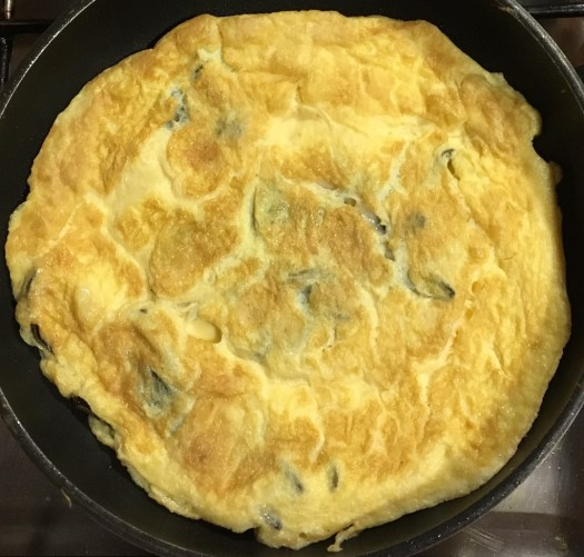 Sage and cheese omelette in a frying pan