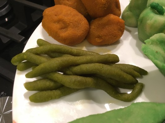 Marzipan shaped as green beans and croquettes