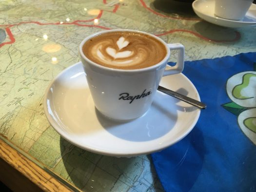 A cup containing an oat milk flat white, over a table with a road map covered with a glass top