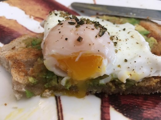 Poached eggs and avocado on toast (close up of luscious yolk)
