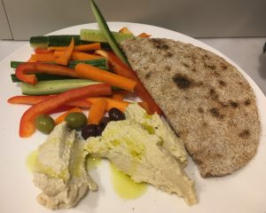 Home made flat bread, and two home made hummus with cucumber, red pepper and carrot slices, with olives