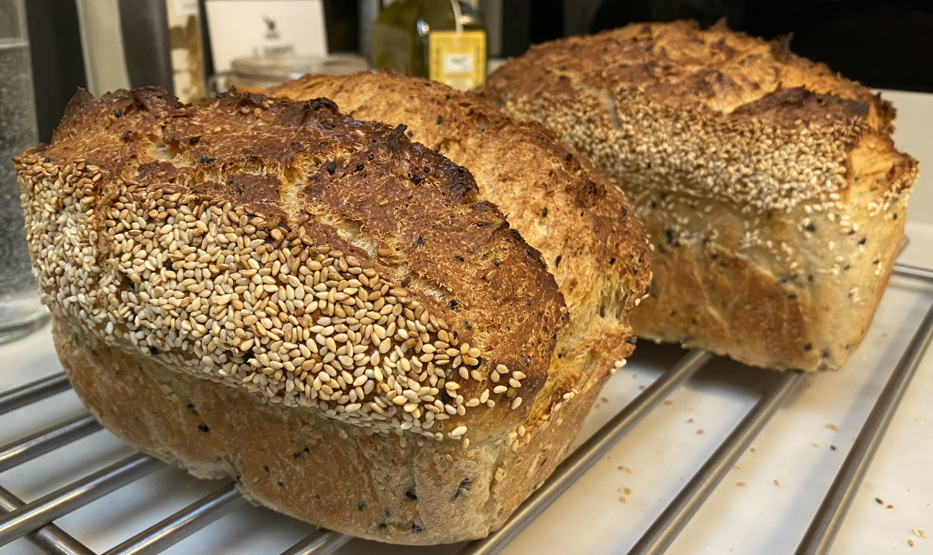 Two sesame seed bread loaves cooling down on a rack