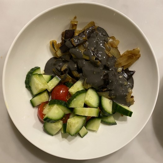 A plate with aubergine shawarma, served with a cucumber and tomato salad and black tahini dressing