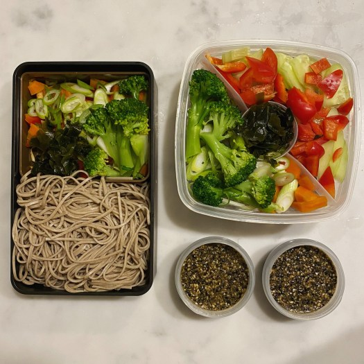 A bento box and a plastic box with a soba noodles salad each, and two smaller recipients with the dressing