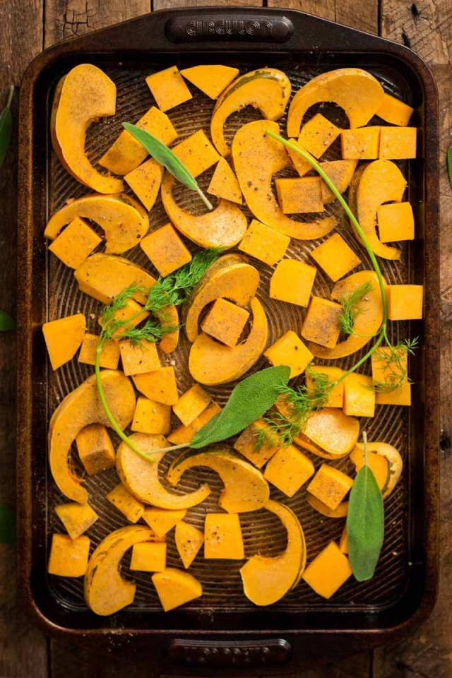 Top-down view of sliced, roasted butternut and sweet dumpling squash on a blackened baking sheet.