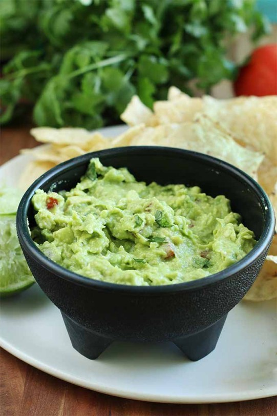 A black plastic molcajete-style bowl filled with homemade guacamole, on a white plate with tortilla chips and a halved and juiced lime, on a brown wood table with fresh cilantro and a tomato in the background.