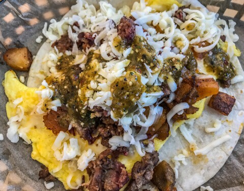 Torchy's Tacos The Wrangler ALL Day Breakfast Taco made with EGGS, POTATOES, SMOKED BEEF BRISKET & CHEESE WITH TOMATILLO SAUCE ON A FLOUR TORTILLA.