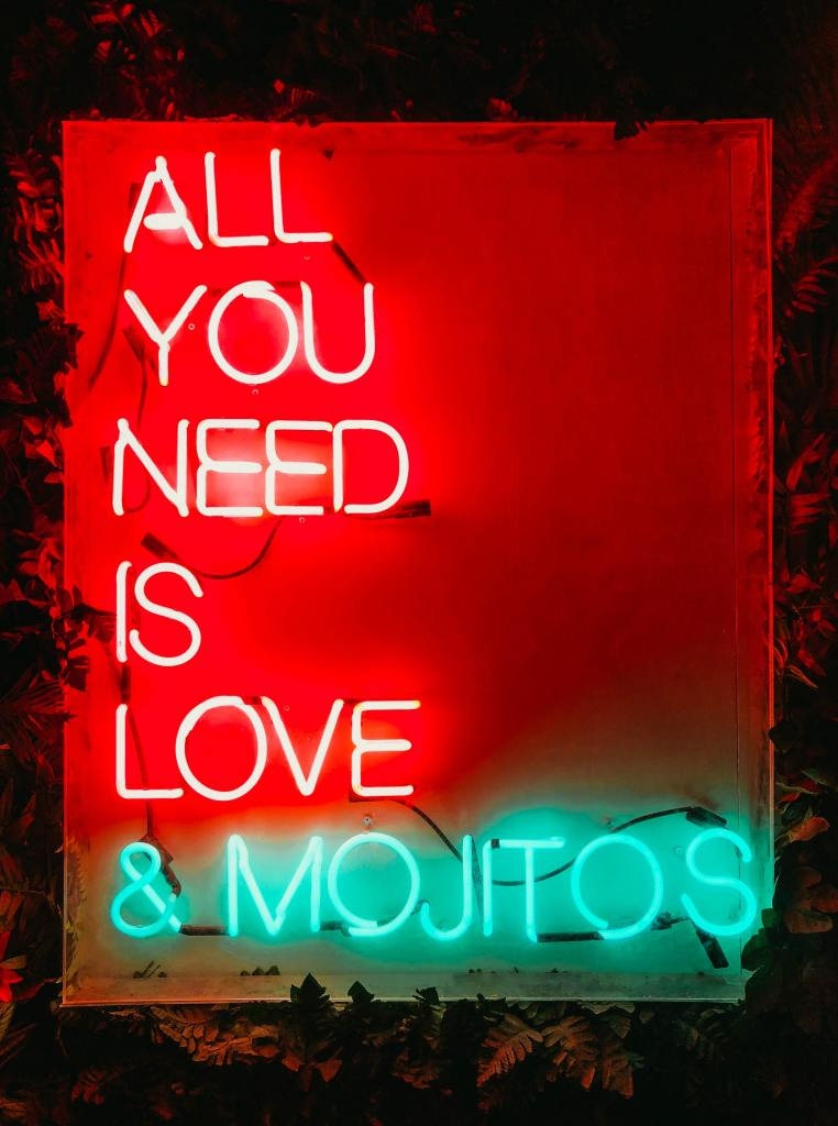 "A neon bar sign that says ""All you need is love & mojitos"""