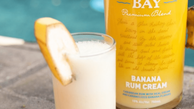 A bottle of Banana Rum Cream and Bananas Foster Shot sitting poolside.
