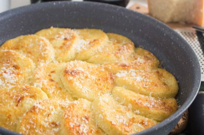 baked semolina gnocchi in a nonstick pan with cheese and wine on the side