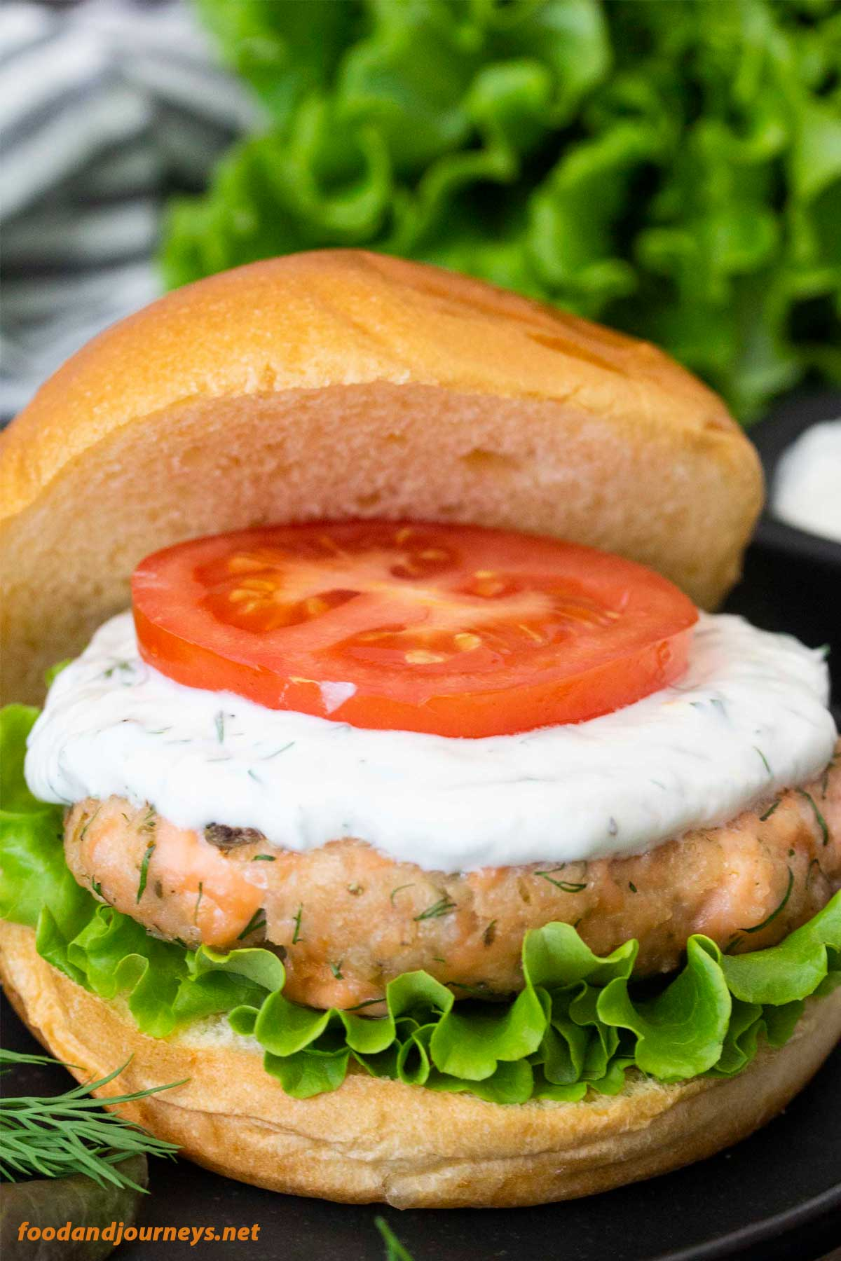 A closer shot of Swedish Salmon Burger with Lemon Yogurt Sauce, highlighting the bits and pieces of the burger.
