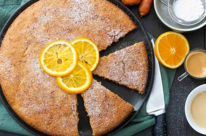 Overhead shot of Carrot and Orange Cake, with a cup of coffee on the side.