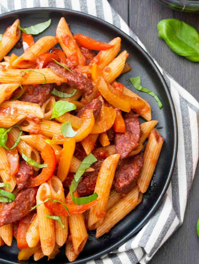 Overhead shot of Pasta with Sausage and Peppers, with yellow and red bell peppers on the side.