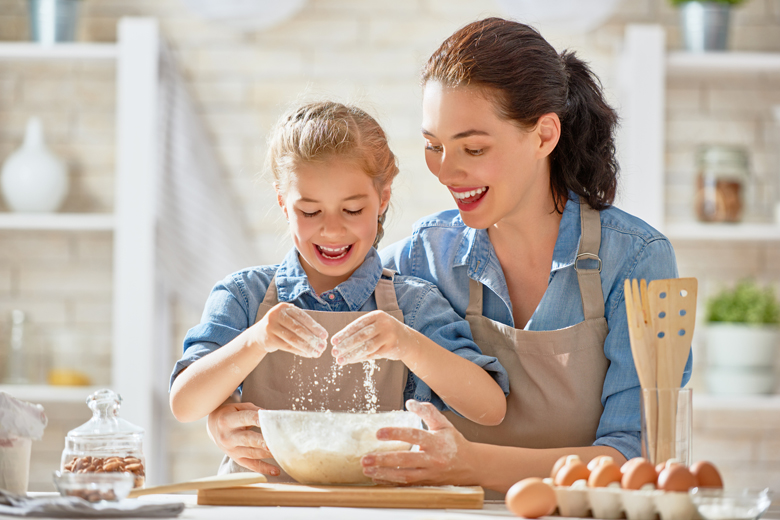 Mother and daughter baking cookies and having fun in the kitchen.