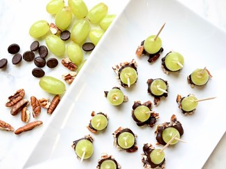 Grapes dipped in dark chocolate and pecans with toothpicks on white plate