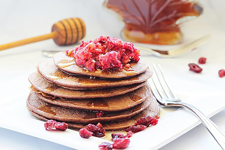 A stack of Dark Chocolate Cranberry Protein Pancakes with fresh raspberries on top