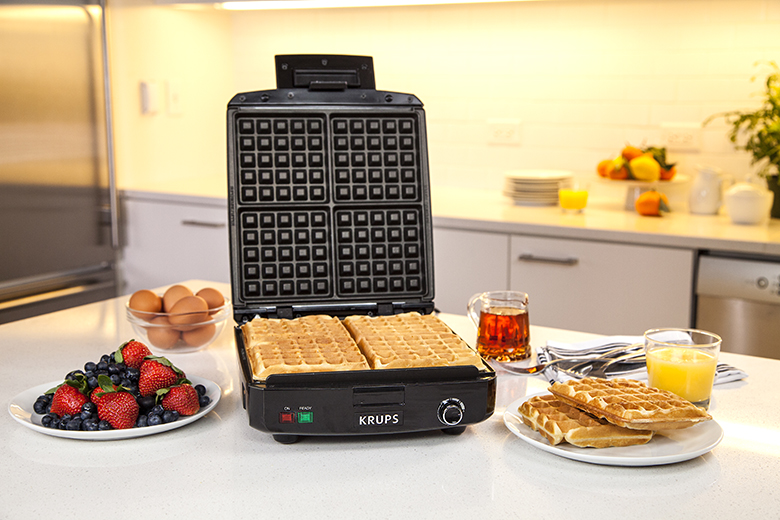 A Krups waffle maker surrounded by breakfast foods on a countertop