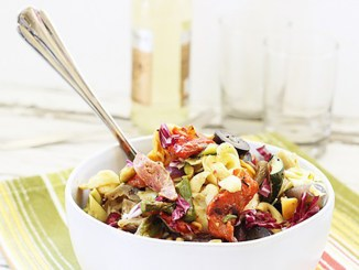 Grilled Vegetable and Tortellini Antipasto Salad in a white bowl with serving spoon