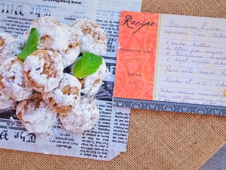 Snowball cookies set on old newspaper clipping with handwritten recipe card nearby