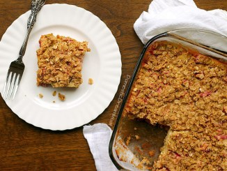 A piece of rhubarb crisp on a plate next to a full dish of same
