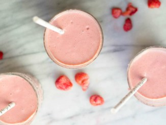 Three pink smoothies with straws on marble countertop sprinkled with raspberries