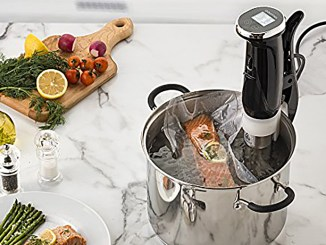 Salmon cooking in a sous vide device on a white marble countertop surrounded by other fresh ingredients
